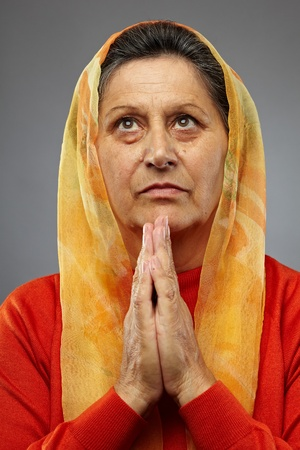 Portrait of a senior caucasian woman praying photo