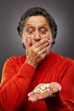 Senior woman inquiets sur la toxicomanie, d'avoir à prendre des pilules de trop nombreux Banque d'images