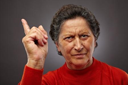 Closeup portrait d'une femme autoritaire hauts sur fond gris