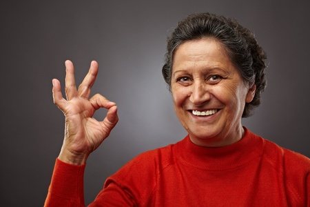 Portrait of a happy senior woman making ok sign photo