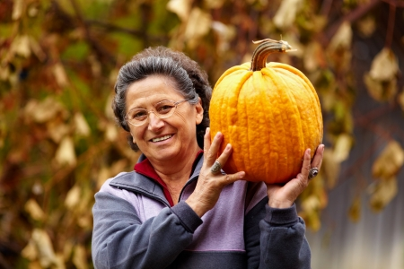 Happy senior woman holding a large yellow pumpkin outdoor