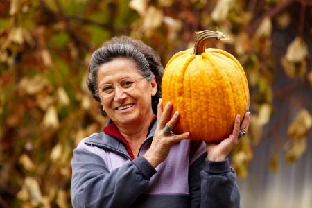 Happy senior woman tenant une grosse citrouille jaune en plein air Banque d'images