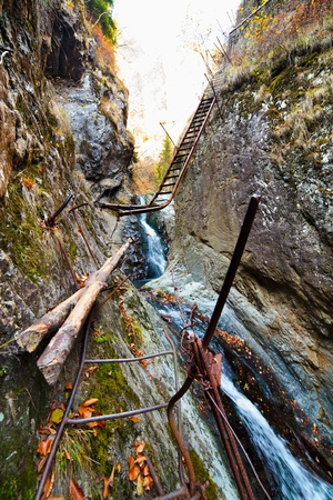 perilous: Perilous mountain passage with ladder over waterfall Stock Photo