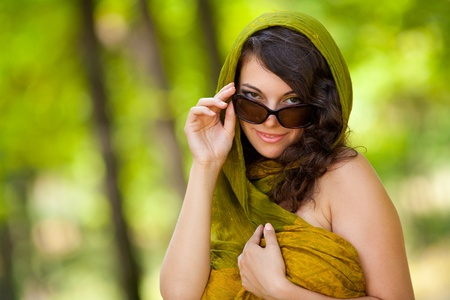 Portrait of a gorgeous young woman with sunglasses in the forest photo