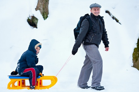 Father and son with a sledge outdoor in the snow photo