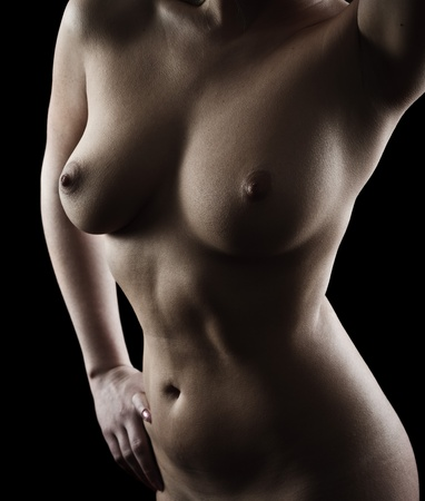 Nude body of a young woman isolated on black background