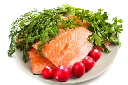 Red salmon fillets on a plate with herbs, isolated on white background photo