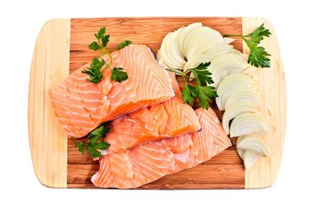 Red salmon fillets with onion and parsley on a wooden board photo