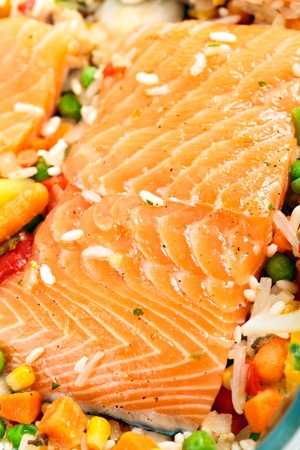 Red salmon fillets garnished with frozen vegetables and herbs photo