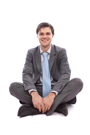 Young businessman sitting on the floor, isolated on white background photo