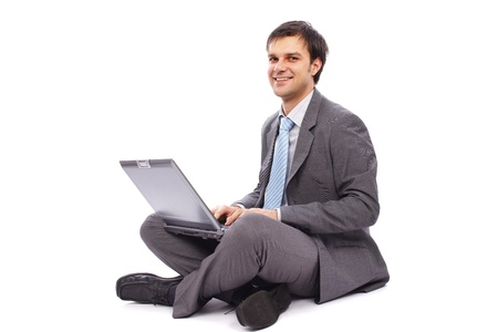 Young businessman sitting on the floor and typing on a laptop photo