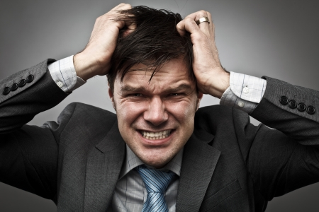 Frustrated young businessman pulling his hair, studio shot