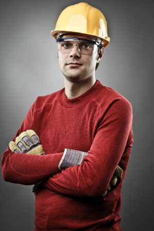 Young blue collar worker with yellow protective helmet and gloves photo