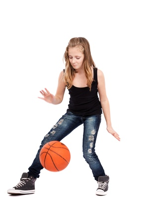 Full length portrait of a girl playing basketball isolated on white background photo