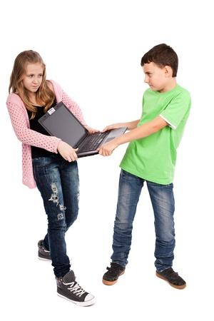 egoista: Ni�os peleando por un ordenador port�til, aisladas sobre fondo blanco Foto de archivo