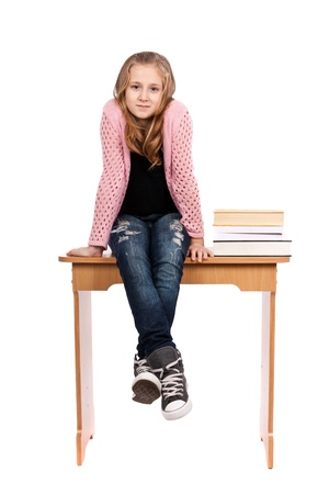 Cute blond schoolgirl sitting on her desk with a pile of books nearby photo