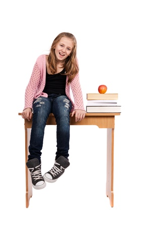 preteen girls: Cute blond schoolgirl sitting on her desk with a pile of books nearby Stock Photo