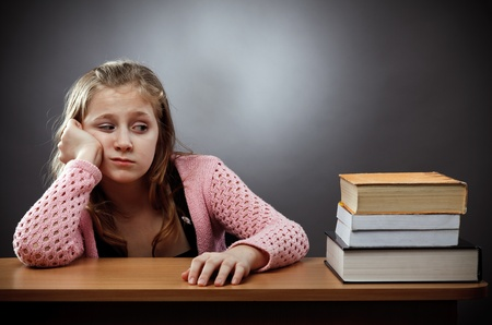 Unhappy caucasian schoolgirl at her desk, near a stack of books Stock Photo