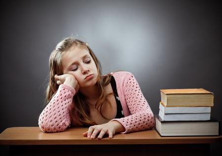 Malheureux écolière caucasien à son bureau, près d'une pile de livres Banque d'images