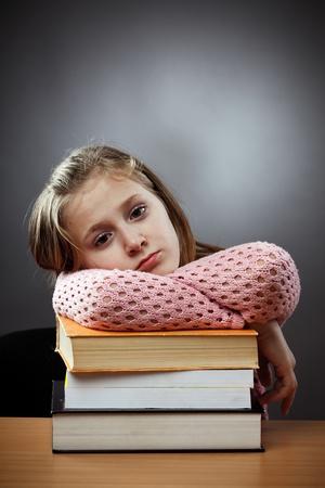 Unhappy caucasian schoolgirl at her desk, near a stack of books photo