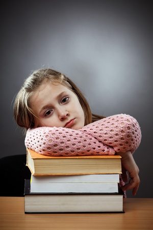 moody background: Unhappy caucasian schoolgirl at her desk, near a stack of books Stock Photo