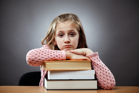 Unhappy caucasian schoolgirl at her desk, near a stack of books photo