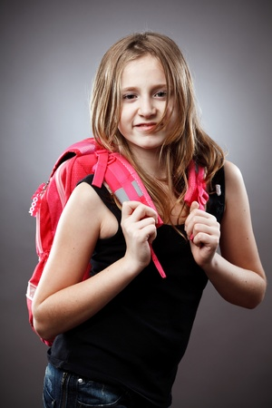 Closeup studio portrait of a blond schoolgirl with pink backpack on gray background photo