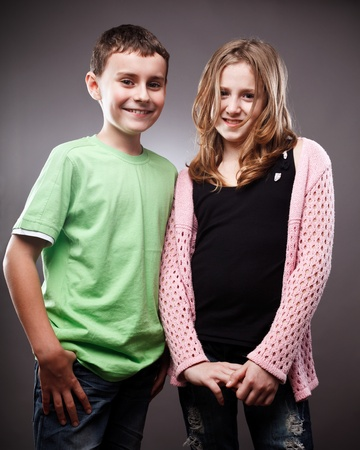 Happy boy and girl on gray background photo