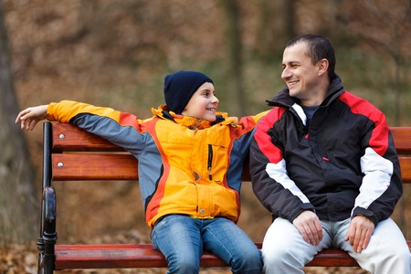 Père et fils assis sur un banc et parler
