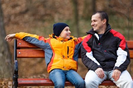 niÑos hablando: Padre e hijo sentados en un banco y hablar Foto de archivo