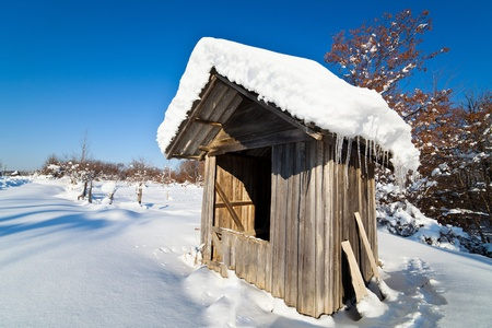 Landscape with wooden shack in the snow, under blue sky photo