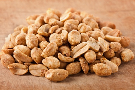 Macro of salted and roasted peanuts on a wooden board Stock Photo - 12223114