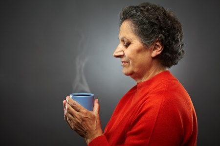 Closeup profile of an elderly senior woman with hot coffee or tea in a cup, on gray background Stock Photo