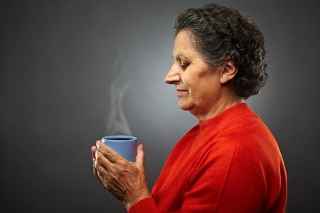Voir le profil Gros plan d'une femme âgée haut avec du café chaud ou un thé dans une tasse, sur fond gris