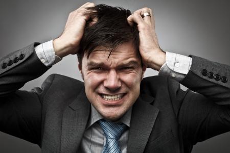 Frustré jeune homme d'affaires lui tirant les cheveux, tourné en studio
