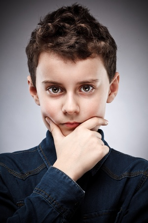 Studio closeup portrait of a boy thinking photo