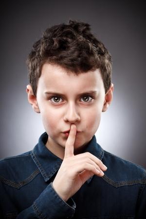 Studio portrait d'un garçon faisant signe silence