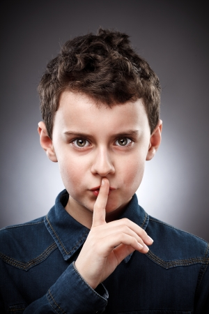 Studio portrait of a boy making silence sign photo