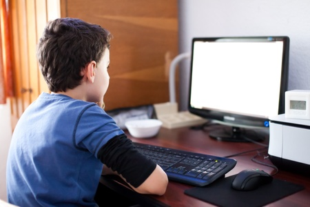 computer printer: Selective focus indoor shot of a boy reading his computers screen Stock Photo