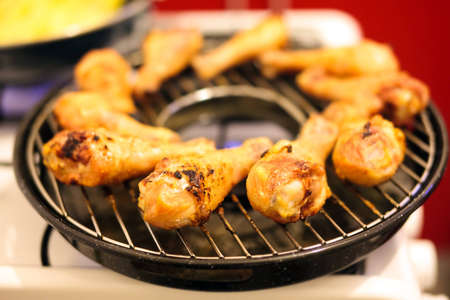 Drumsticks on a grill on gas stove photo