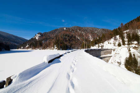 Landscape with foot tracks on a dam frozen lake in the mountains photo