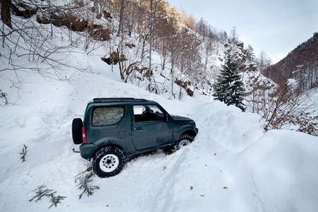 heap snow: 4x4 car being stuck in a snow avalanche in a canyon