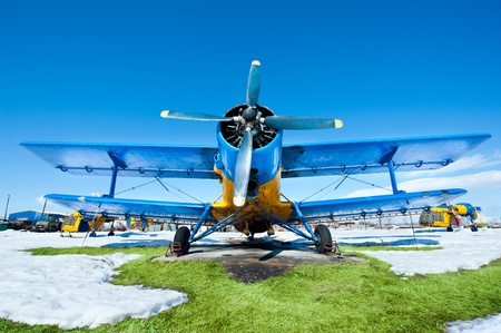 Old airplanes parked on a meadow with snow in a sunny day