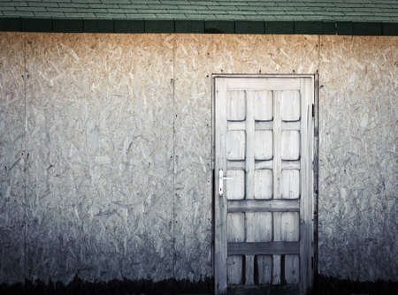 Old rural wooden door on a wooden wall with copyspace Stock Photo - 12575394