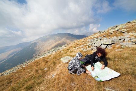 Mother and son resting in mountains and reading a map photo