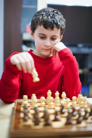 playing chess: Closeup portrait of a school boy playing chess, selective focus Stock Photo