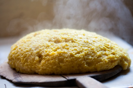 Hot polenta on wooden board, steaming