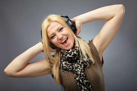 Studio portrait of a beautiful blond young woman with headphones photo
