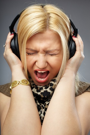 Closeup of a young blond woman with headphones singing or shouting while listening music photo