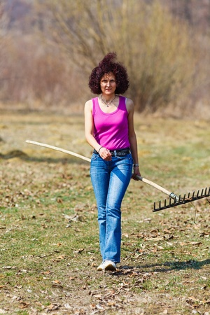 Young woman with a rake spring cleaning in a walnut orchard Stock Photo - 13029819
